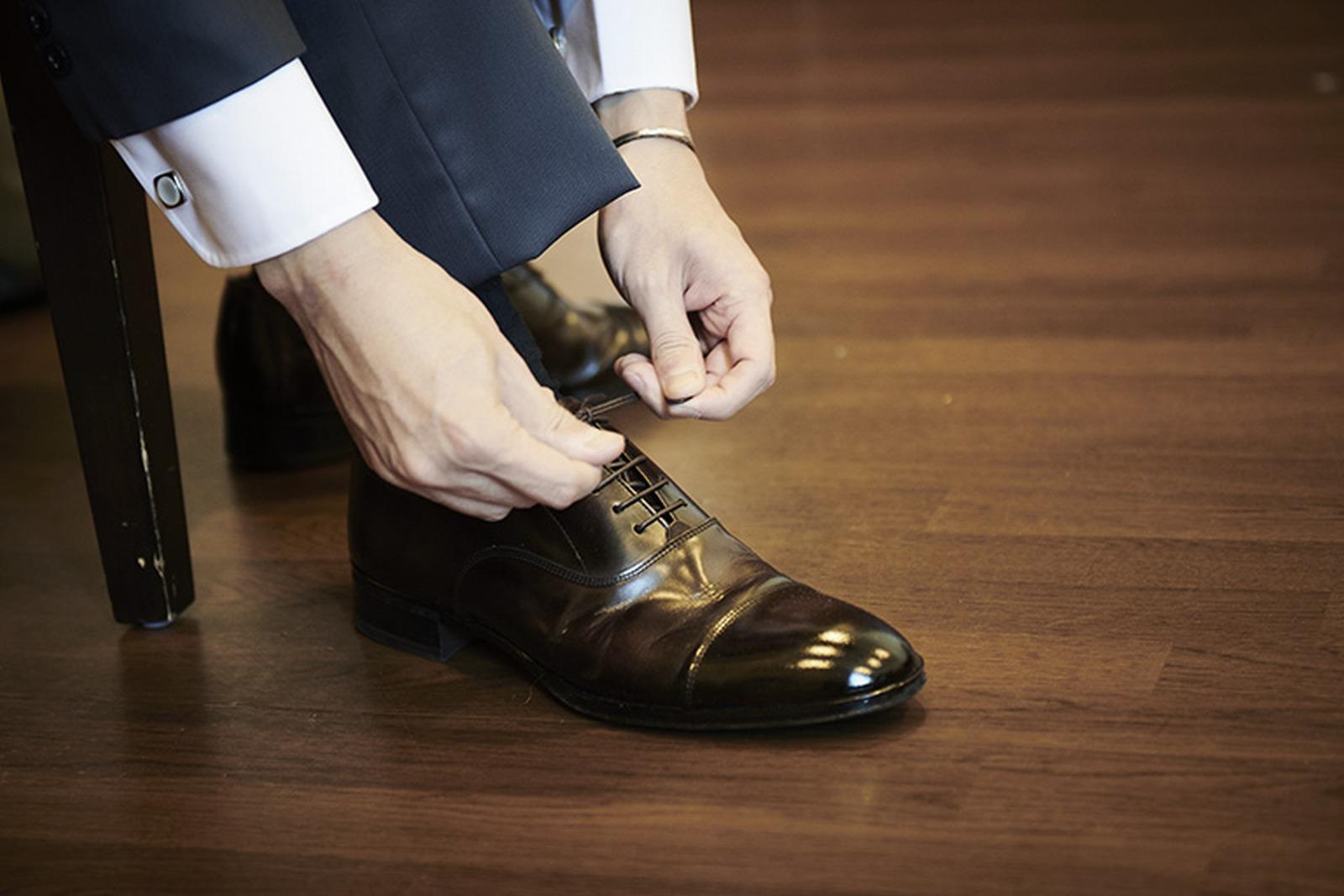 徳島県の結婚式場ブランアンジュで靴ひもを結び支度をする新郎