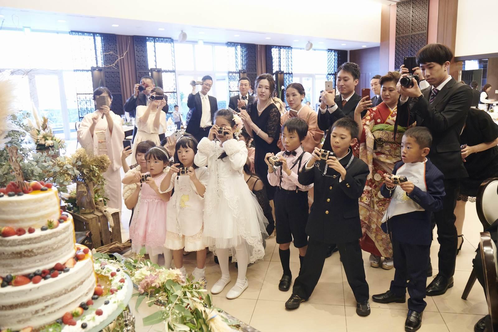 徳島県の結婚式場ブランアンジュでウエディングケーキ入刀を撮影するゲスト
