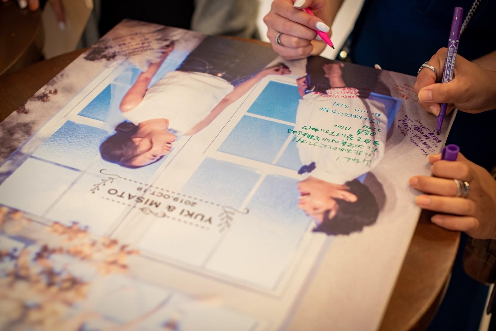 徳島市の結婚式場ブランアンジュでウェルカムボードにメッセージを記入するゲスト