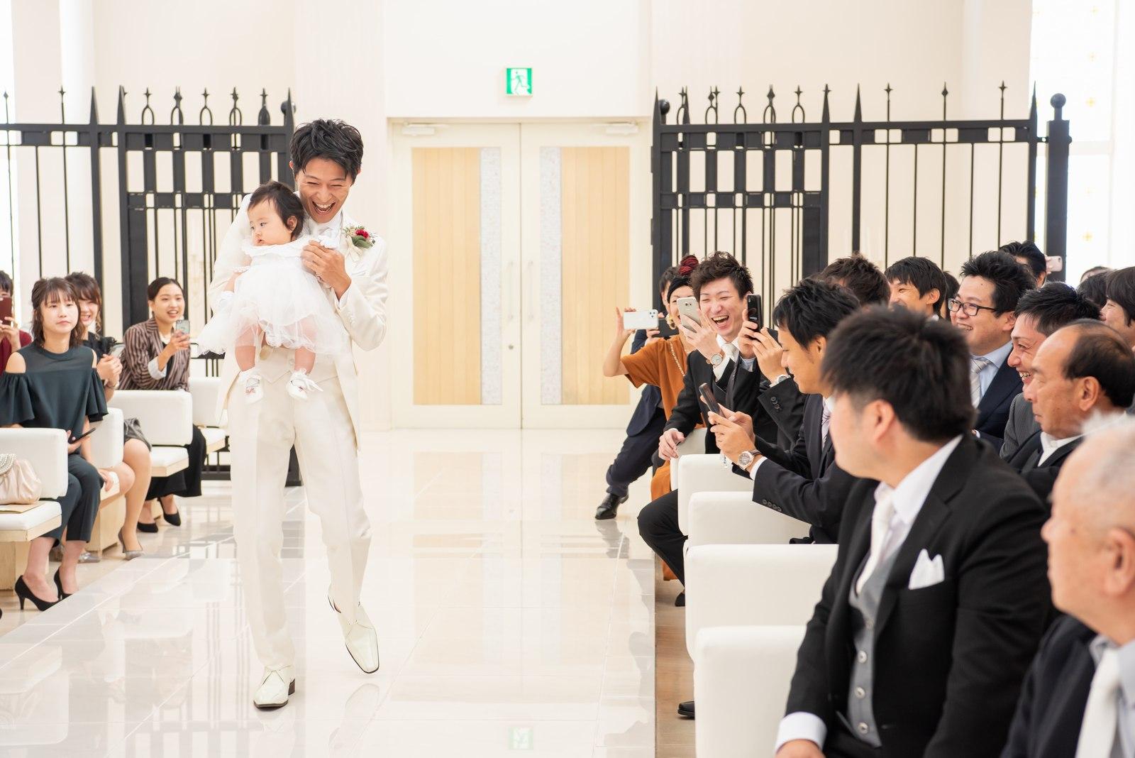 徳島市の結婚式場ブランアンジュで子どもを抱きながらチャペル入場する新郎