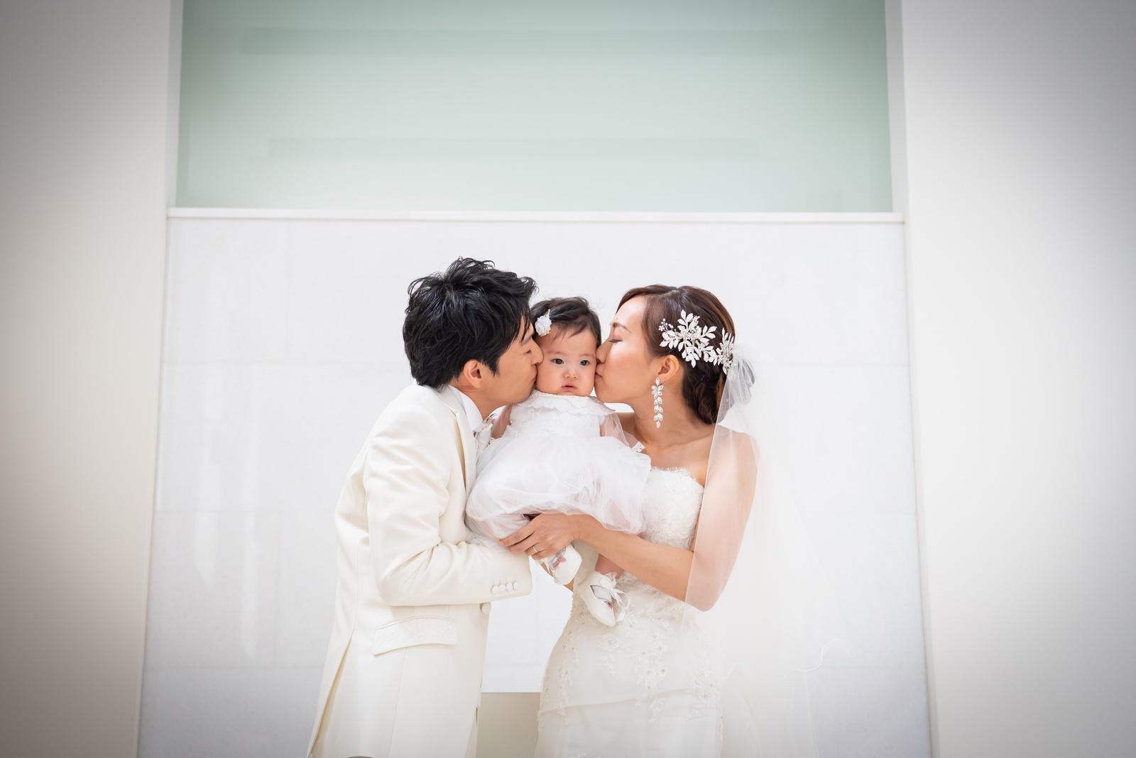 徳島市の結婚式場ブランアンジュでお子様をはさんで誓いのキスを交わす新郎新婦