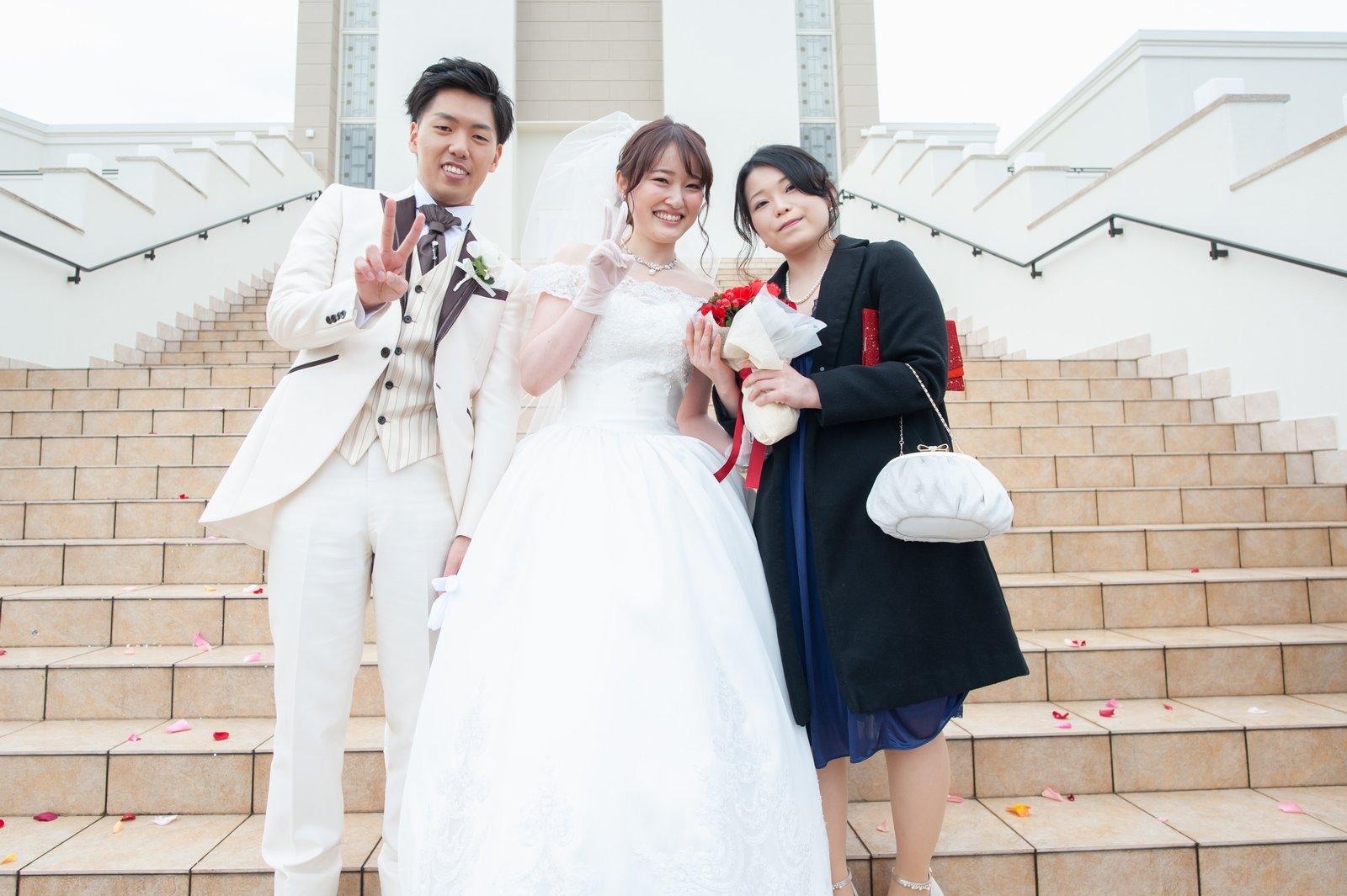 徳島市の結婚式場ブランアンジュでブーケをキャッチしたゲストと記念写真をとる新郎新婦
