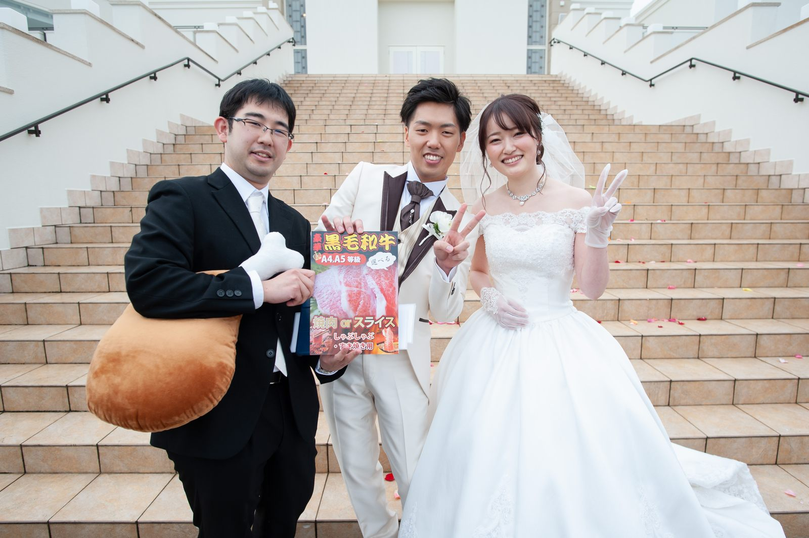 徳島市の結婚式場ブランアンジュのアフターセレモニーでお肉をキャッチしたゲストと記念写真をとる新郎新婦