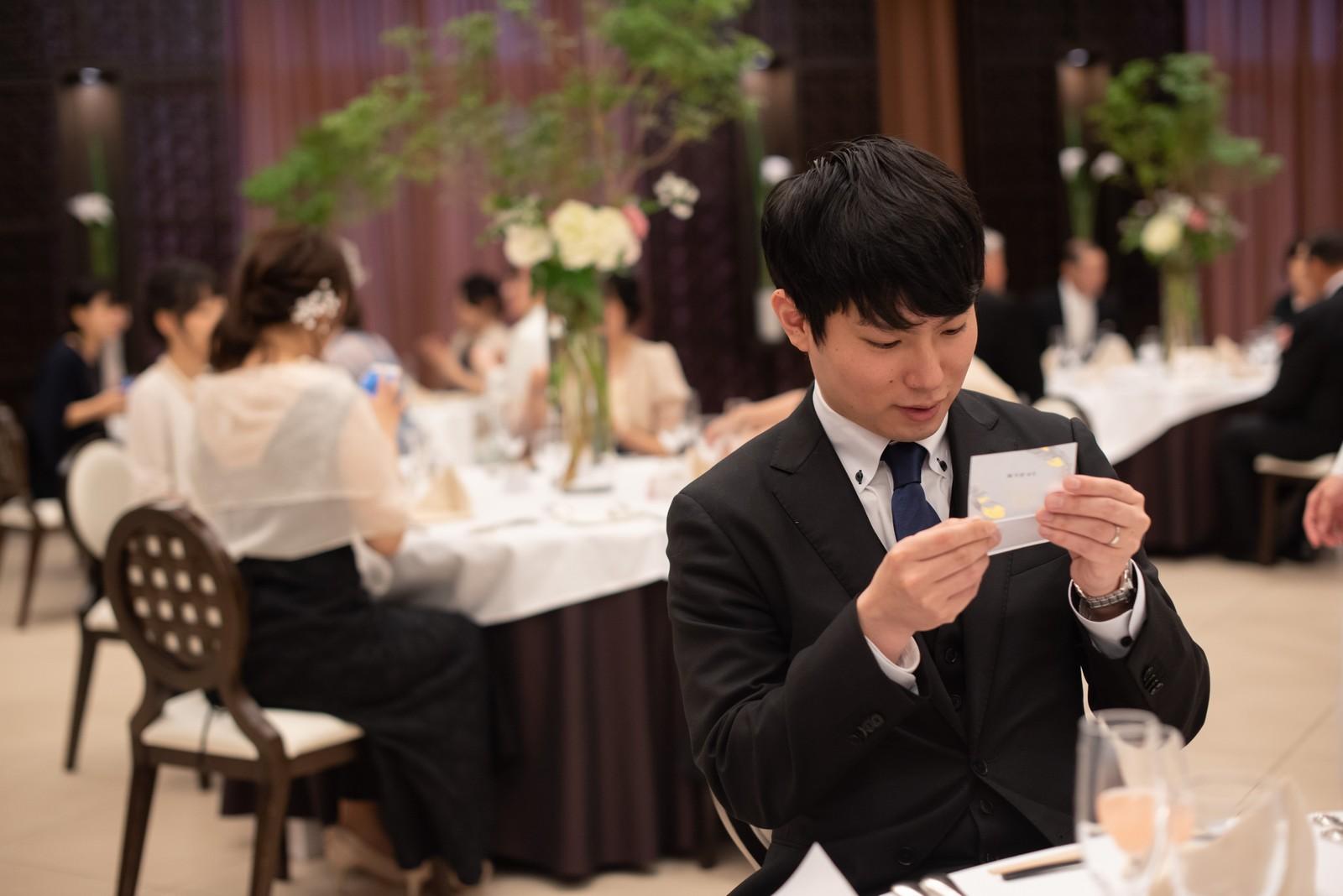 徳島市の結婚式場ブランアンジュで新郎新婦手作りの席札に書かれたメッセージを読むゲスト