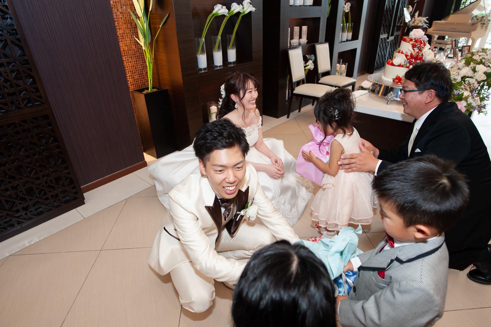 徳島市の結婚式場ブランアンジュの披露宴会場でゲストの子どもたちにプレゼントを渡す新郎新婦