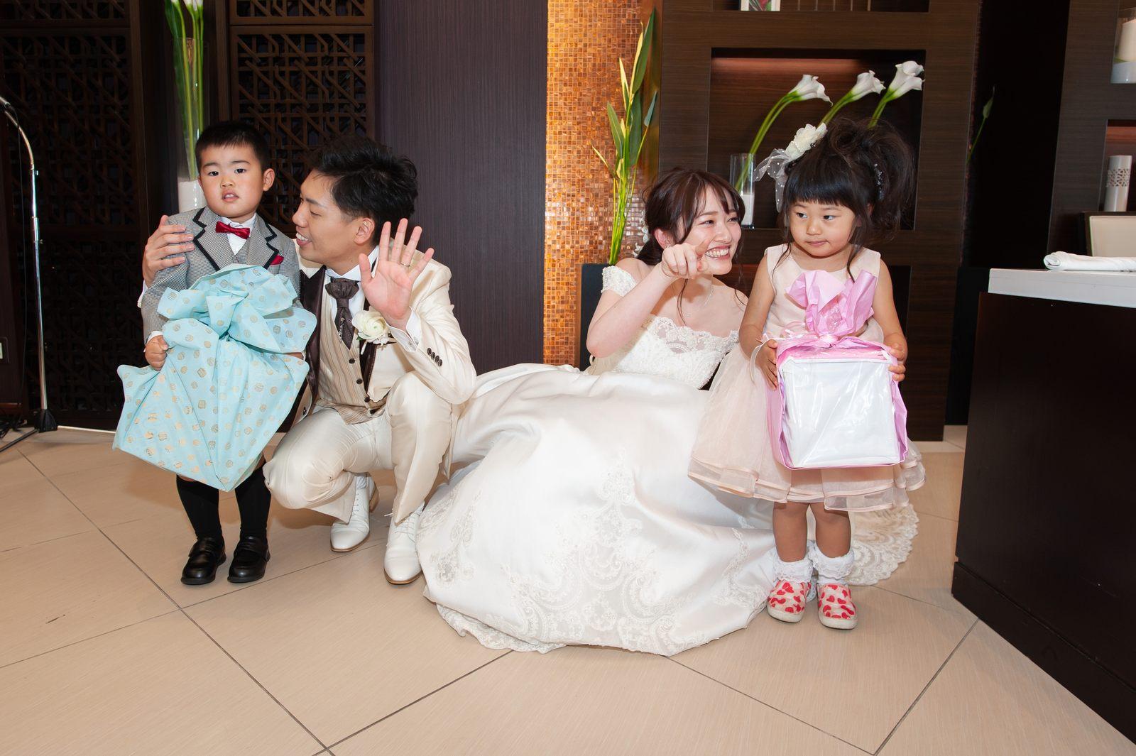徳島県の結婚式場ブランアンジュでプレゼントを持った子どもたちと写真に写る新郎新婦