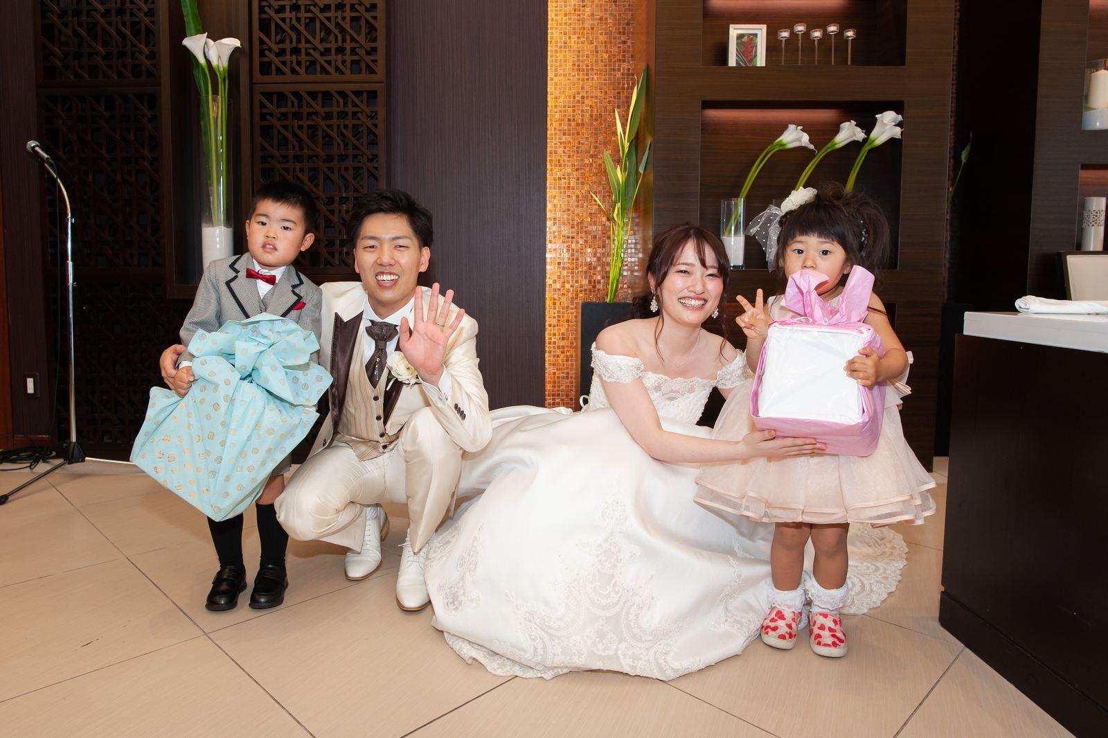 徳島市の結婚式場ブランアンジュの披露宴会場でお子様ゲストと笑顔で写真を撮影する新郎新婦