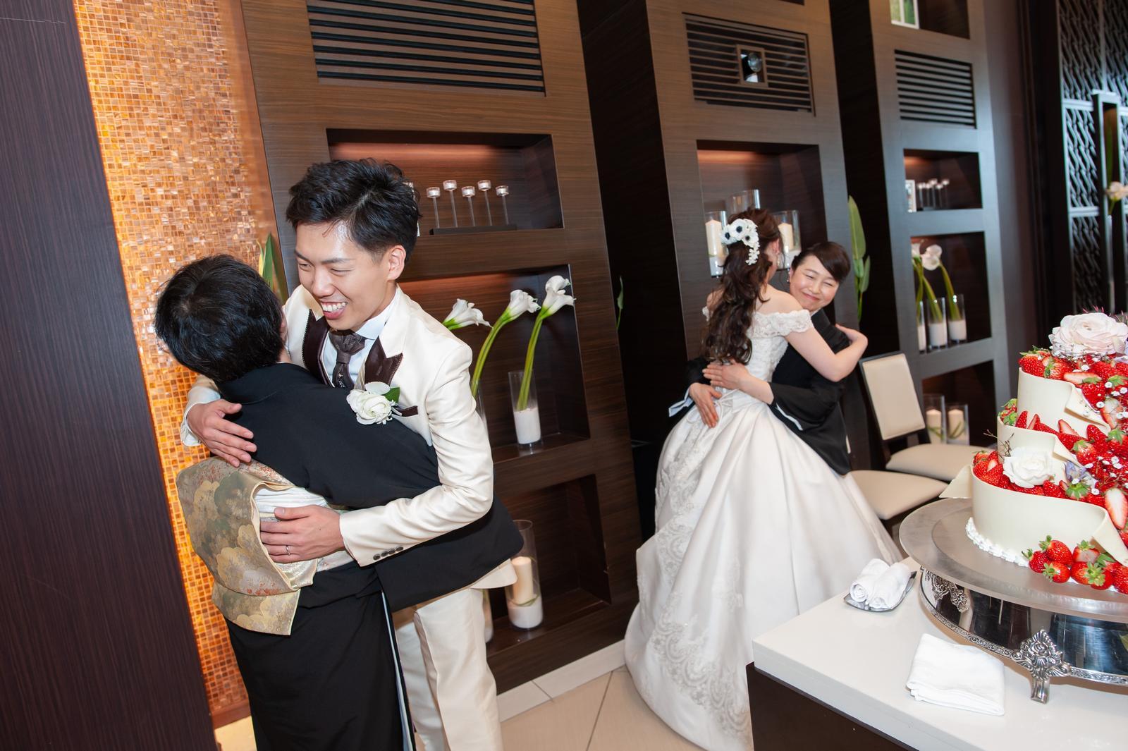 徳島県の結婚式場ブランアンジュで母と抱き合う新郎新婦