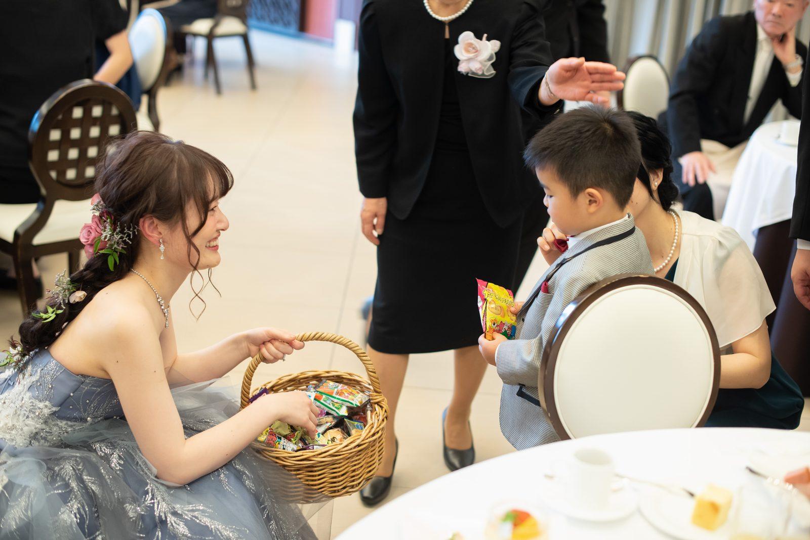 徳島市の結婚式場ブランアンジュの披露宴会場でビールサーブとともにおつまみを配る新婦