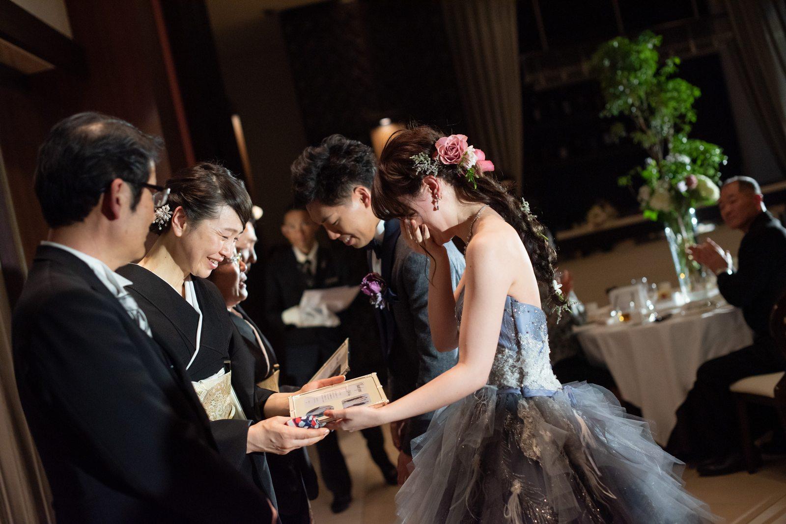 徳島市の結婚式場ブランアンジュの披露宴で両親に前写しと記念写真が入った写真立てをおくる新郎新婦