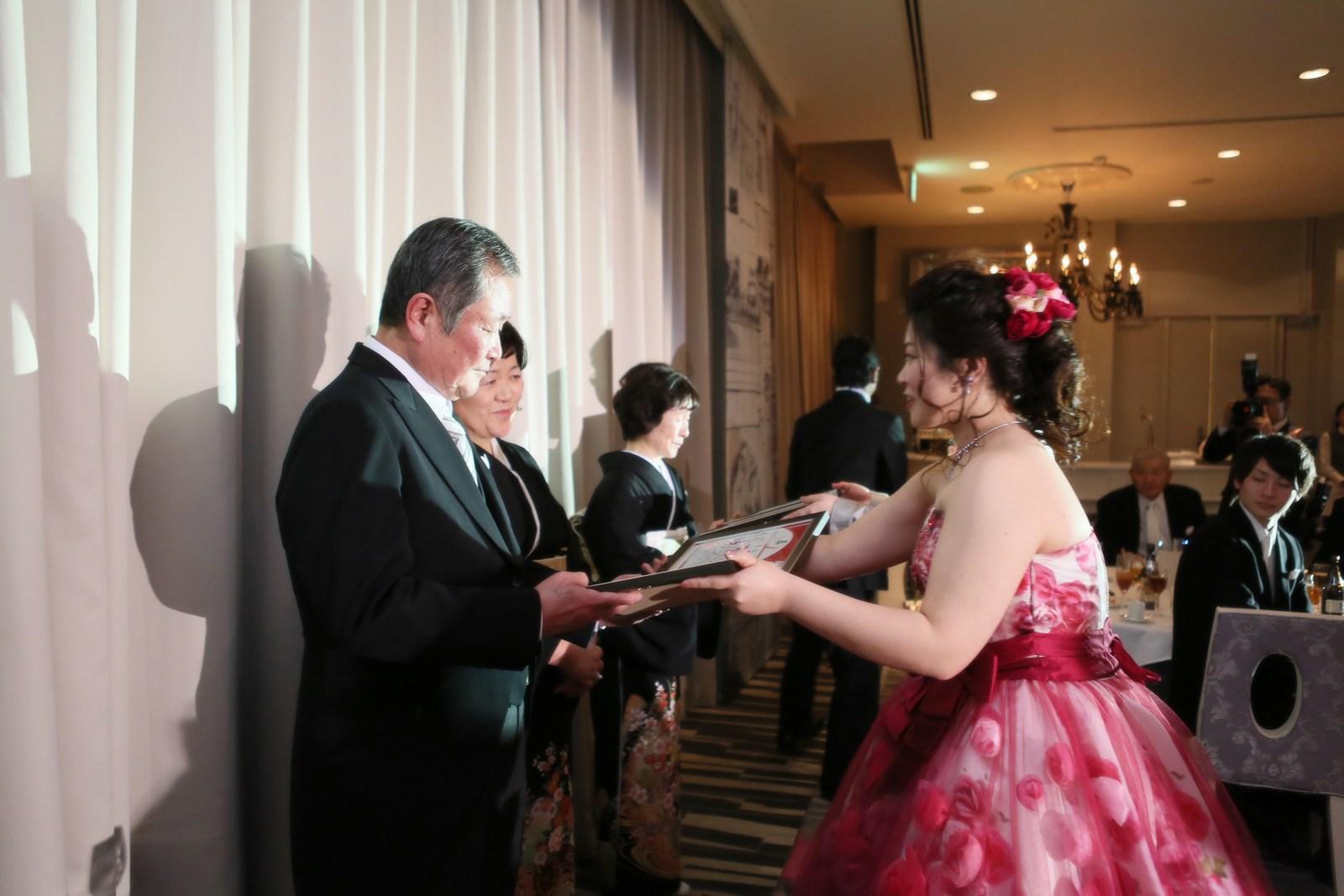 徳島市の結婚式場ブランアンジュの披露宴会場で親御様に感謝の気持ちがこもったプレゼントを渡す新郎新婦