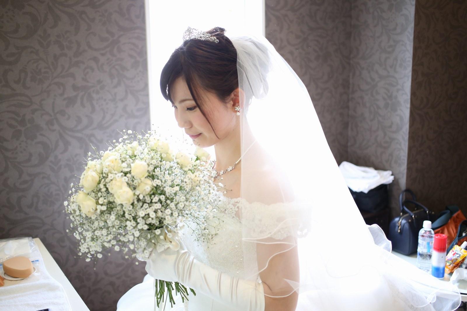 徳島市の結婚式場ブランアンジュでマリエでバラ・かすみ草のブーケを見つめる新婦