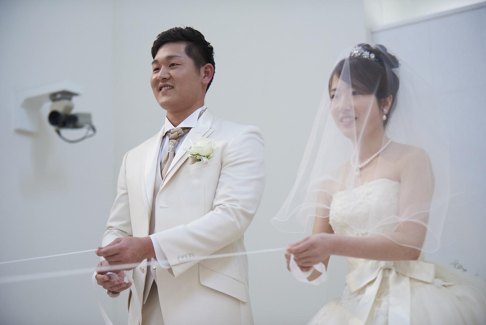 徳島市の結婚式場ブランアンジュでリングキッズが乗る歩行器をリボンで引っ張る新郎新婦様