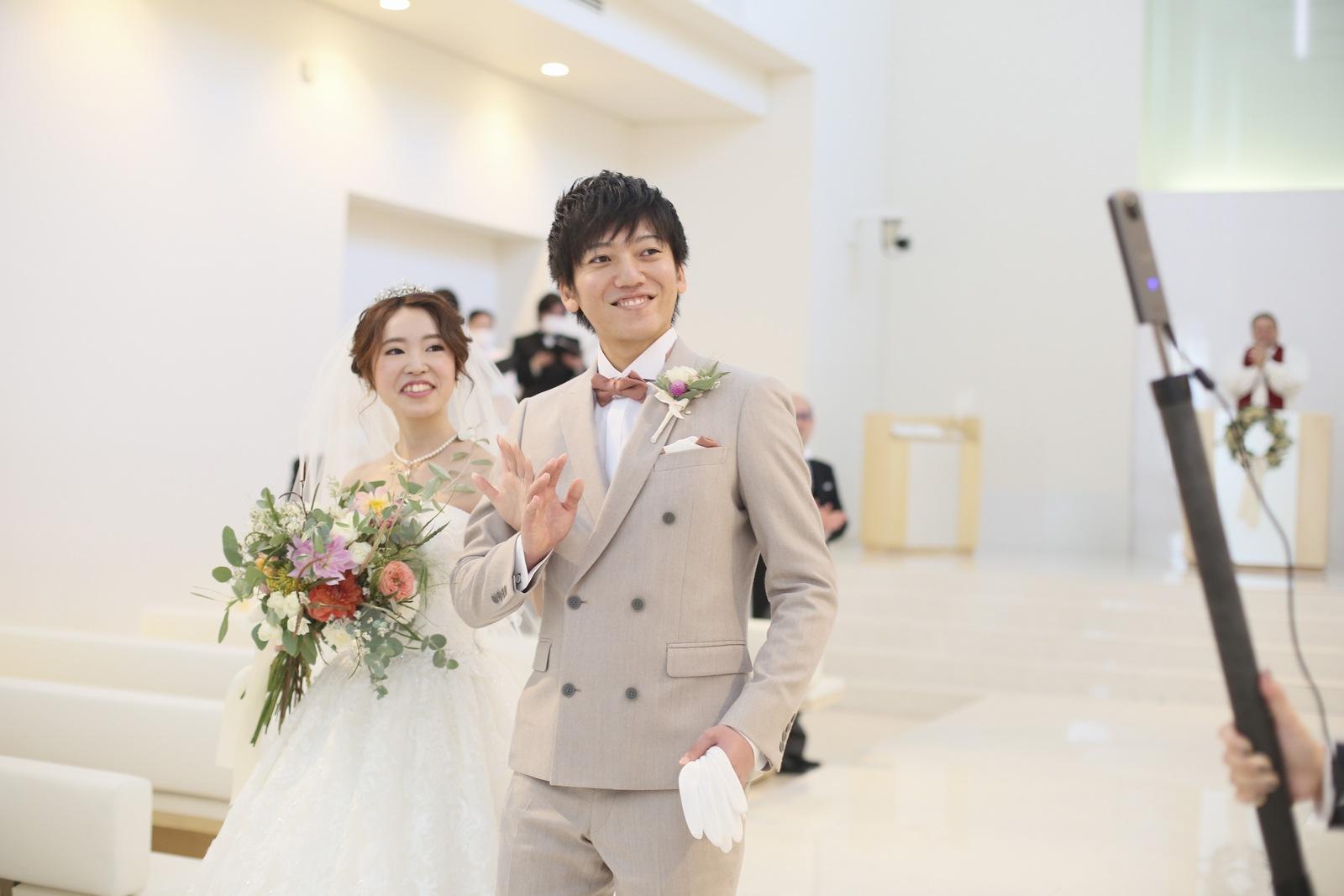 徳島市の結婚式場ブランアンジュでチャペルから退場しながら映像越しにゲストへ挨拶する新郎新婦