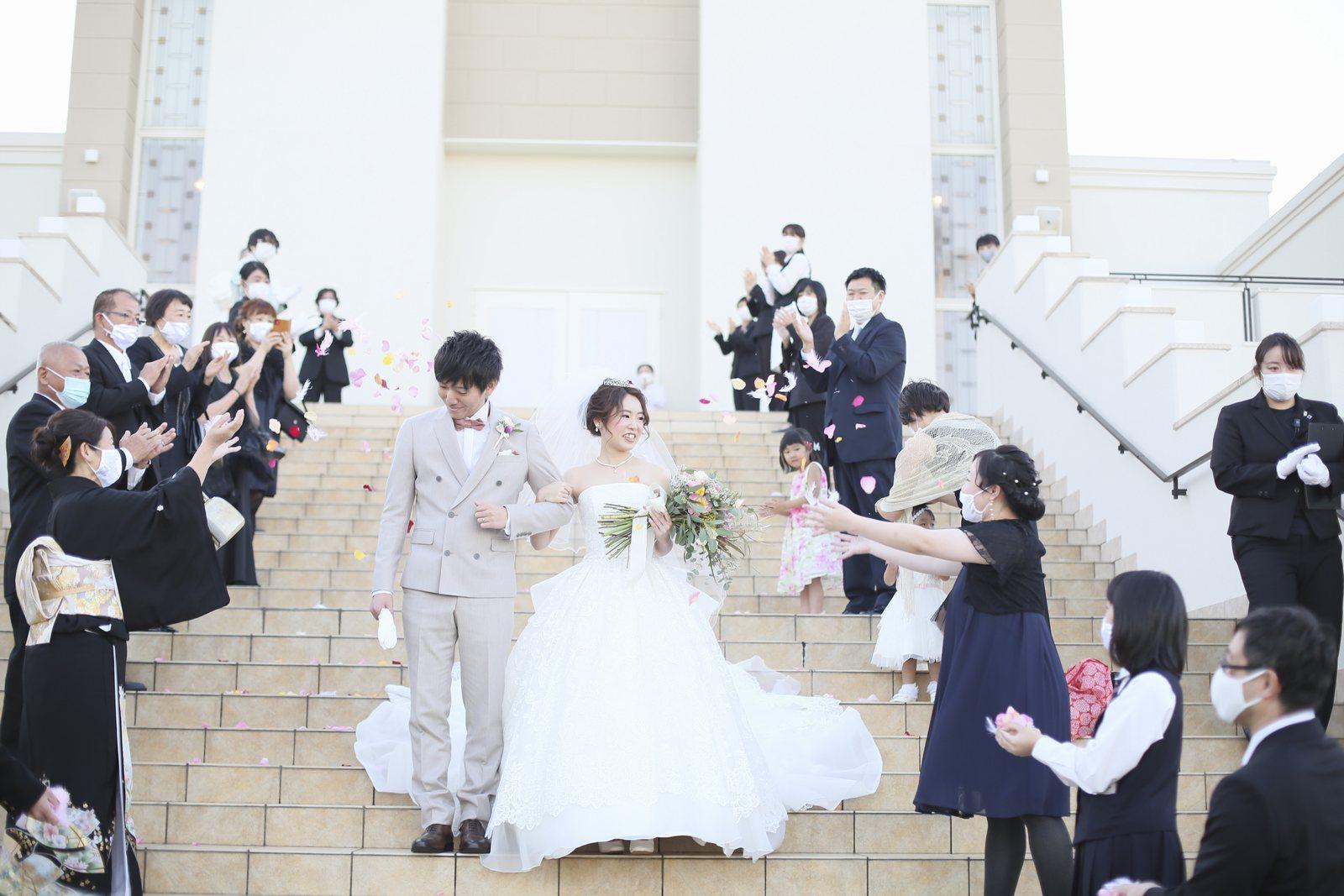 徳島県の結婚式場ブランアンジュの大階段でフラワーシャワーの祝福を受ける新郎新婦