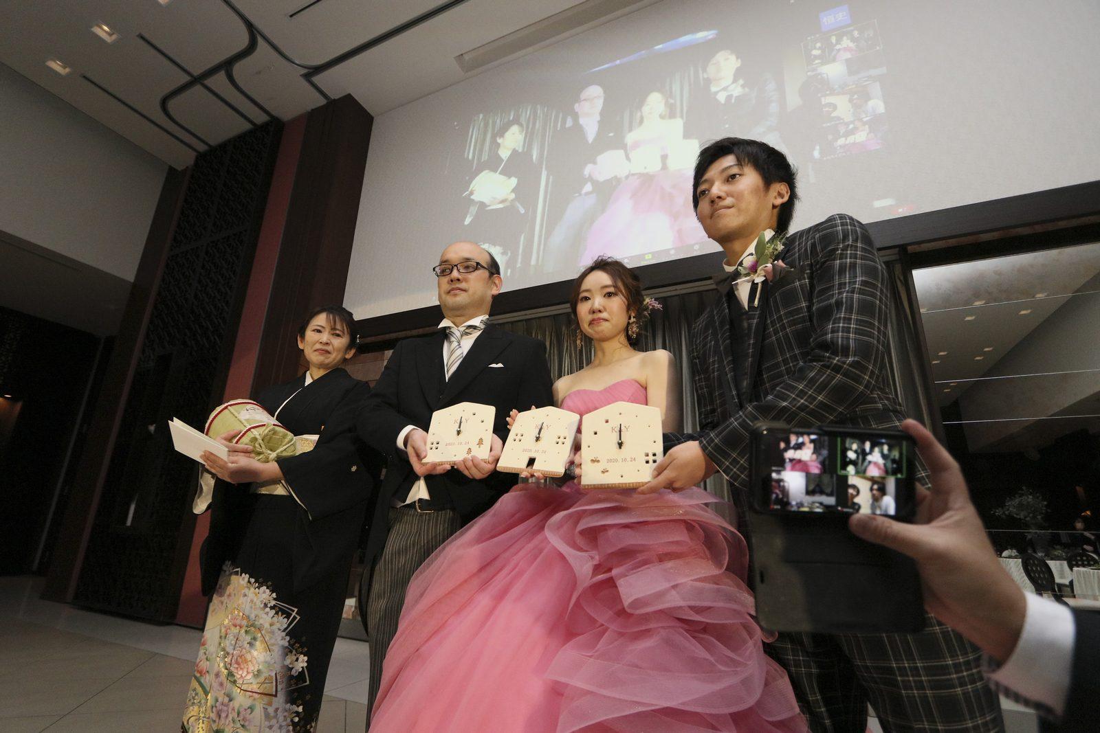 徳島市の結婚式場ブランアンジュで贈呈された信楽焼の絆時計を持ち記念写真をとる新郎新婦と新婦両親