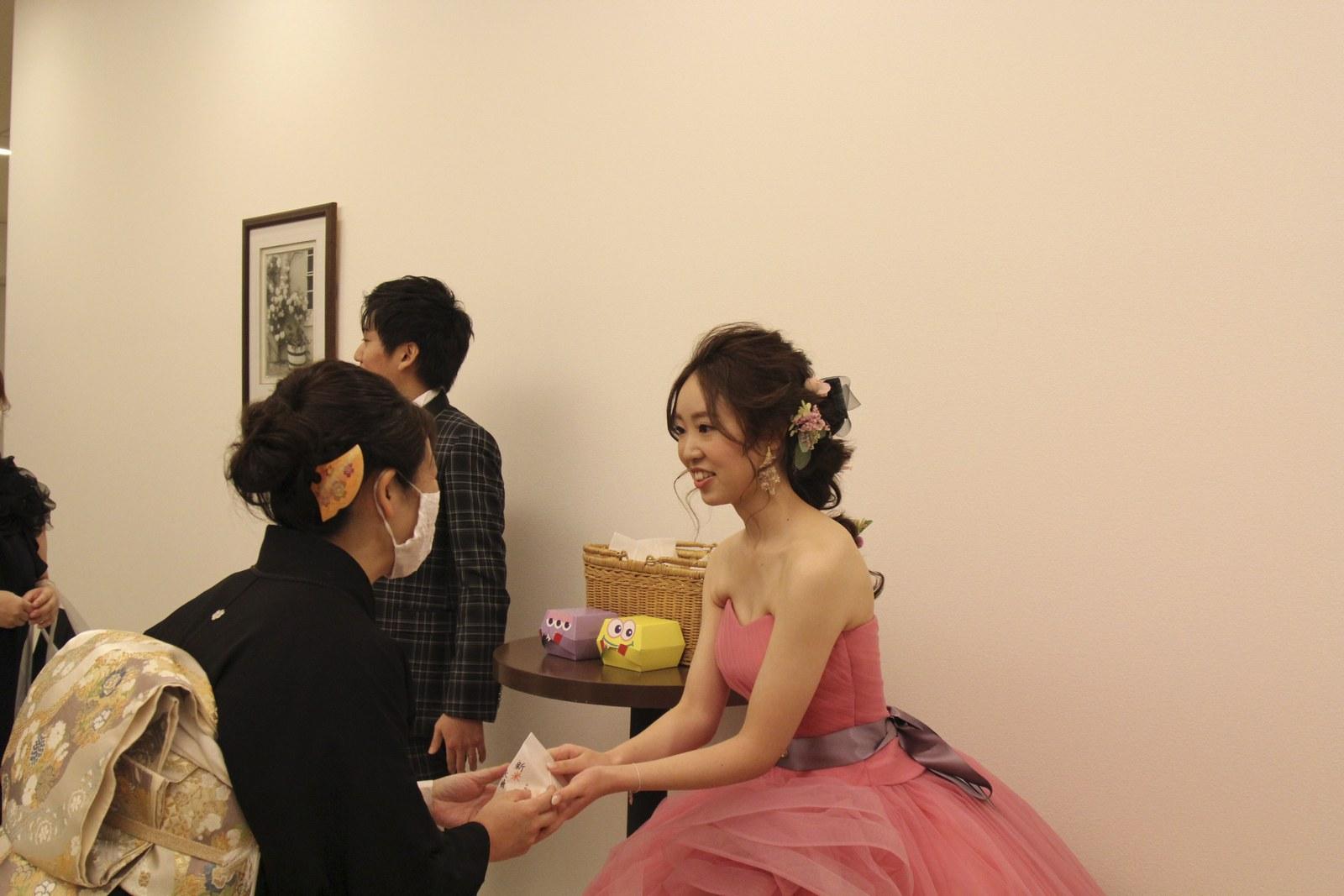 徳島市の結婚式場ブランアンジュの送賓でお見送り品をゲストに渡す新婦