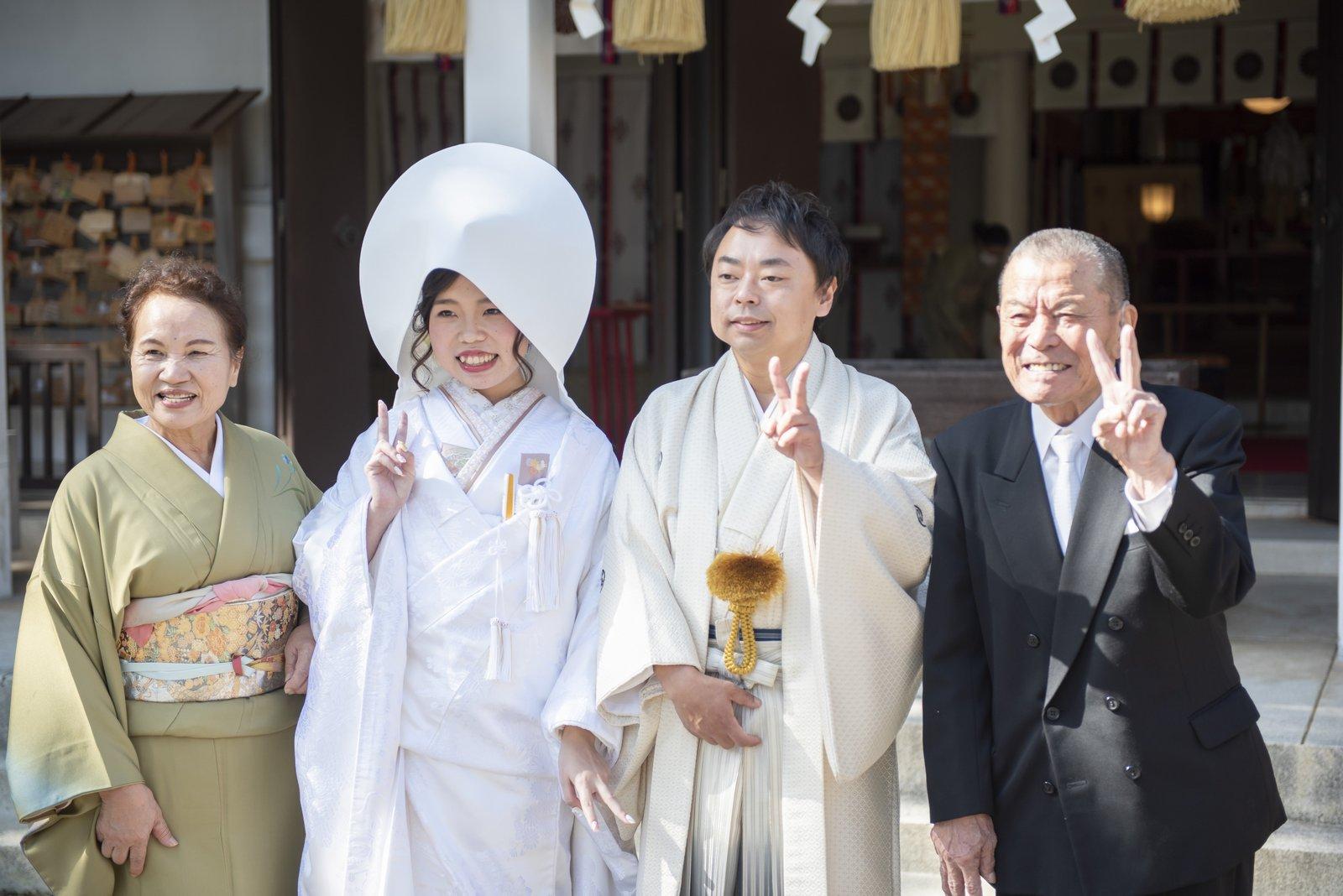 徳島市の結婚式場ブランアンジュで披露宴を行う前に挙式をした忌部神社で親族と記念写真を撮影する新郎新婦