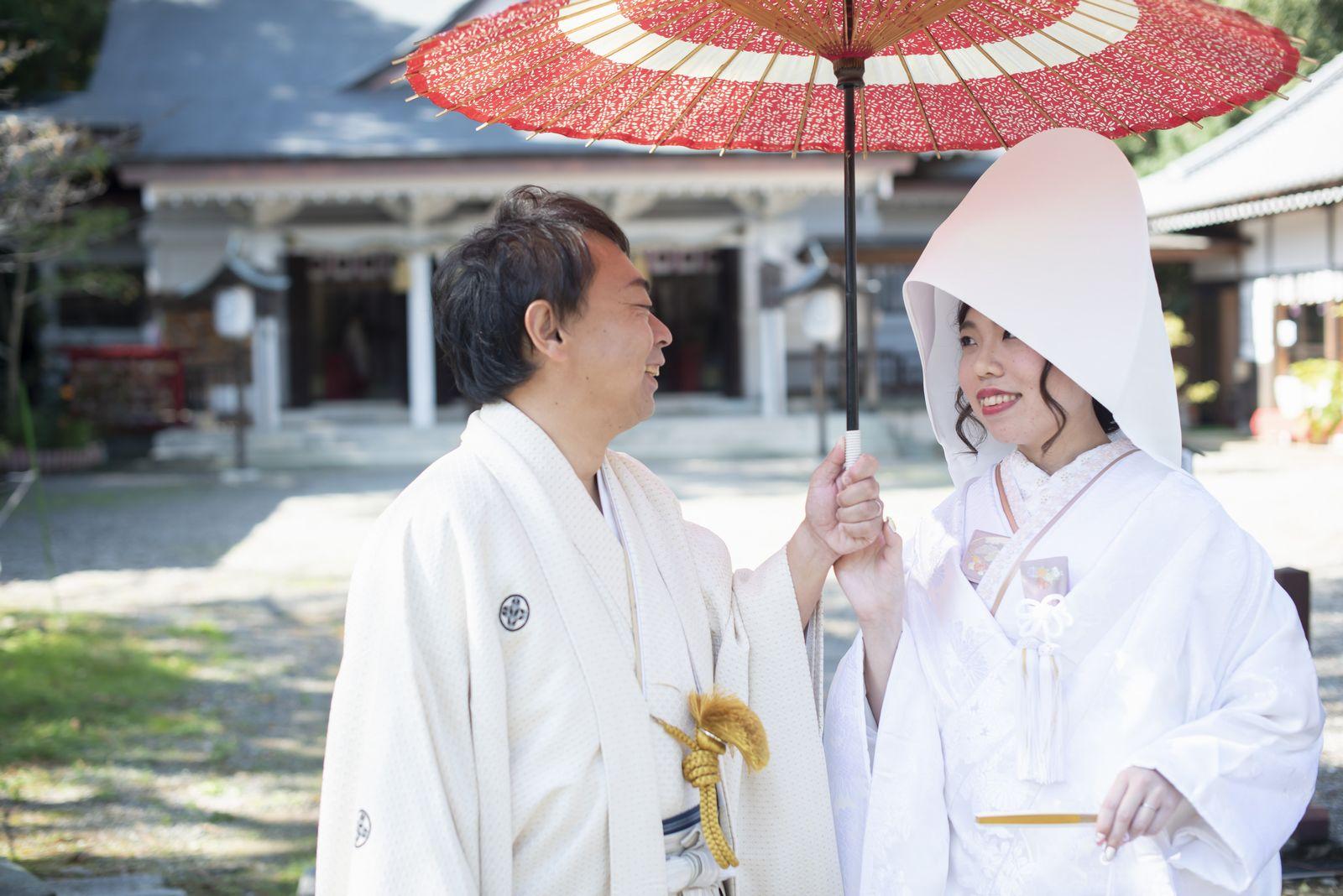 徳島市の結婚式場ブランアンジュで披露宴を行う前に挙式をした忌部神社で番傘をさして写真を撮影する新郎新婦
