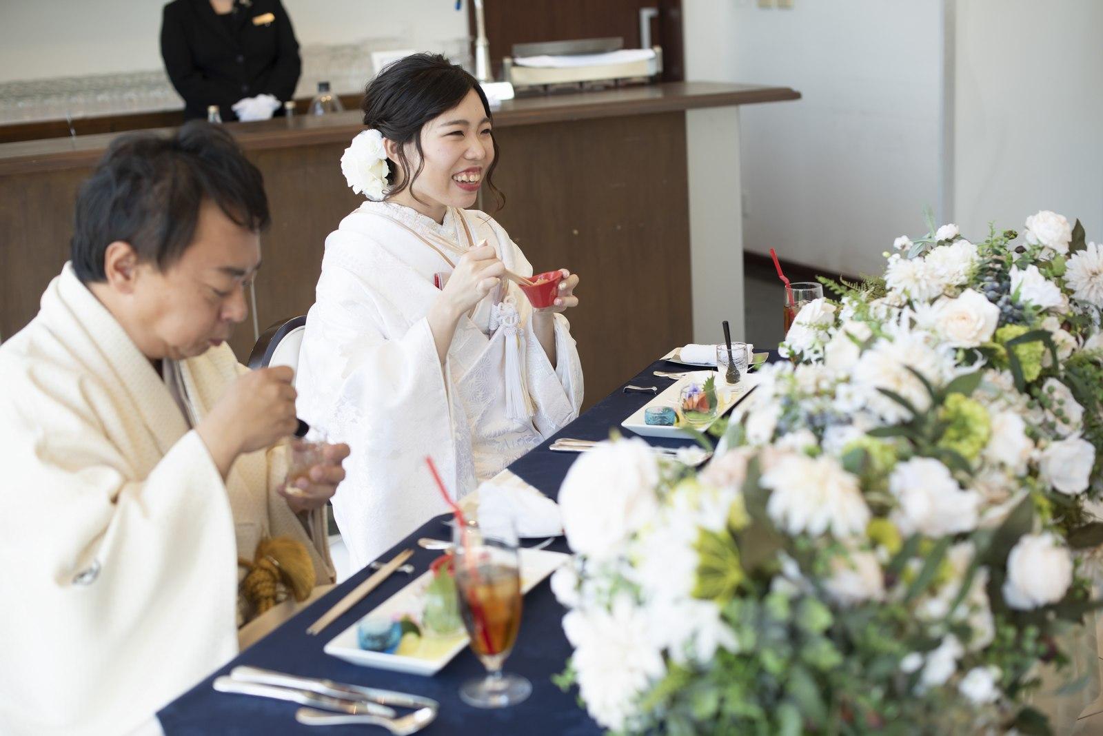 徳島市の結婚式場ブランアンジュの披露宴会場で食事をしながらゲストと楽しそうに話す新婦